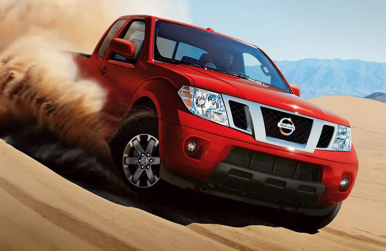red 2016 nissan frontier driving through desert dunes