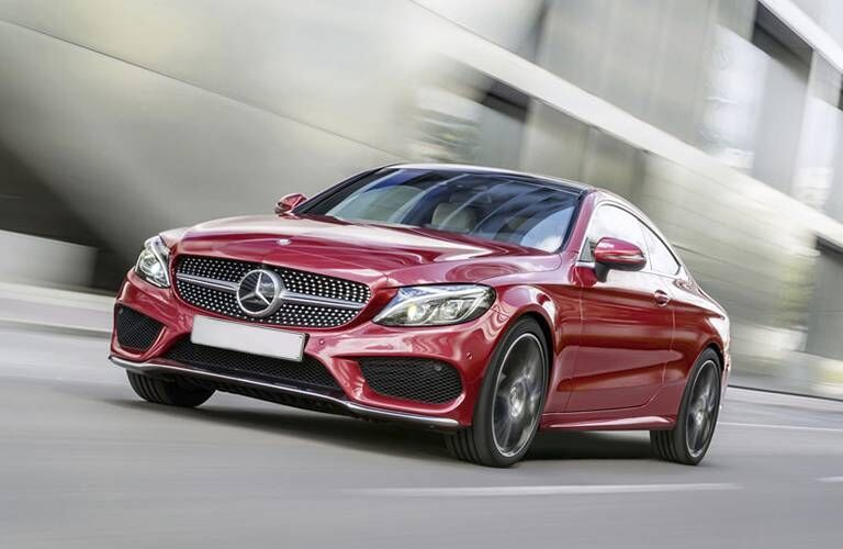 Exterior view of a red 2017 Mercedes-Benz C-Class Coupe driving down a city street