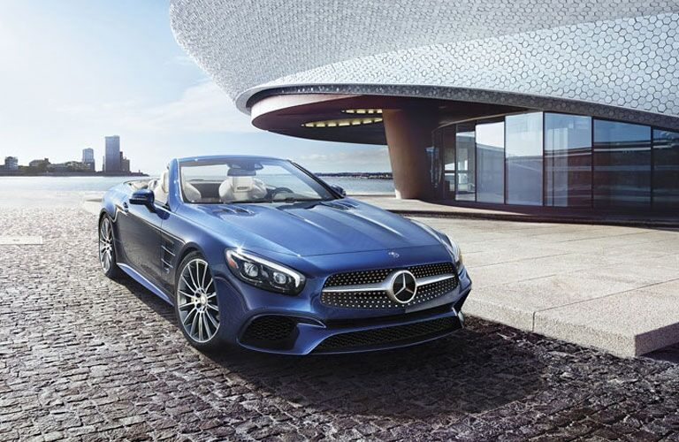 Exterior view of a blue 2017 Mercedes-Benz CL Roadster parked in the driveway of a modern home