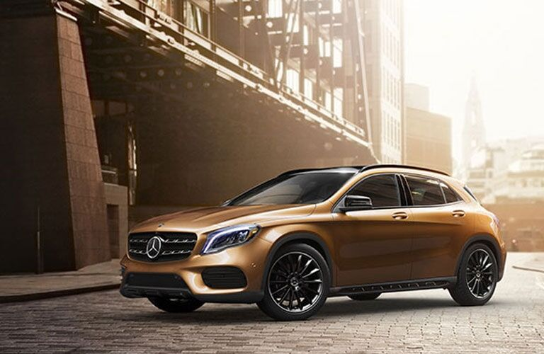 Exterior view of a bronze 2017 Mercedes-Benz GLA SUV parked on a city street