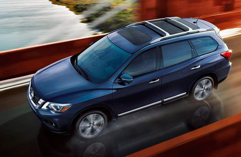 blue 2017 nissan pathfinder driving over bridge