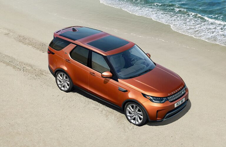Orange 2018 Land Rover Discovery Driving on a Beach