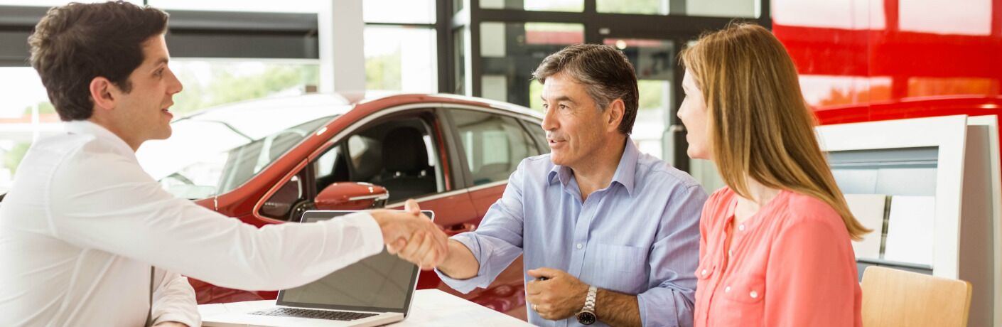 A couple sitting at a desk and buying a car from a car salesman