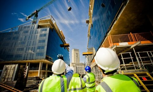 Men working on a construction site view of them from the back looking up at buildings
