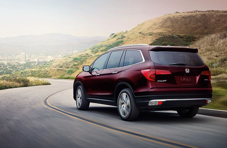 Maroon 2017 Honda Pilot drives down a winding mountain road.