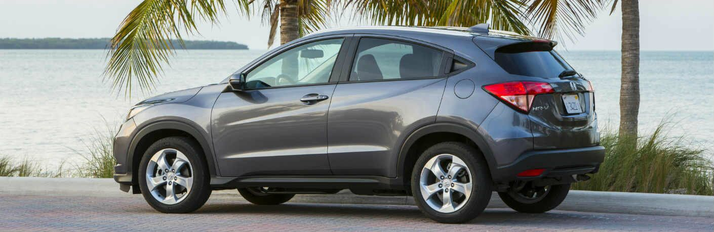 2017 Honda HR-V parked under a palm tree by a body of water.