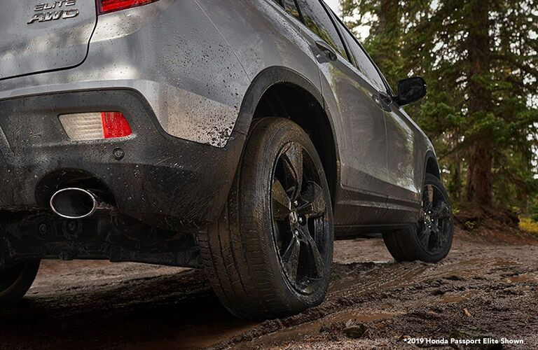 Muddy low-angle view of the tires and bottom of a Honda Passport