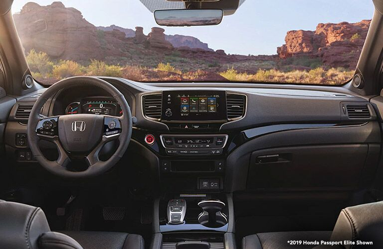 Front interior of a Honda Passport with a view of rugged southwestern US nature