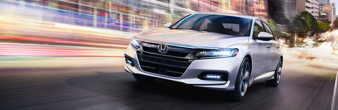 White 2020 Honda Accord Touring cruises up a road with a stylized blur of color.