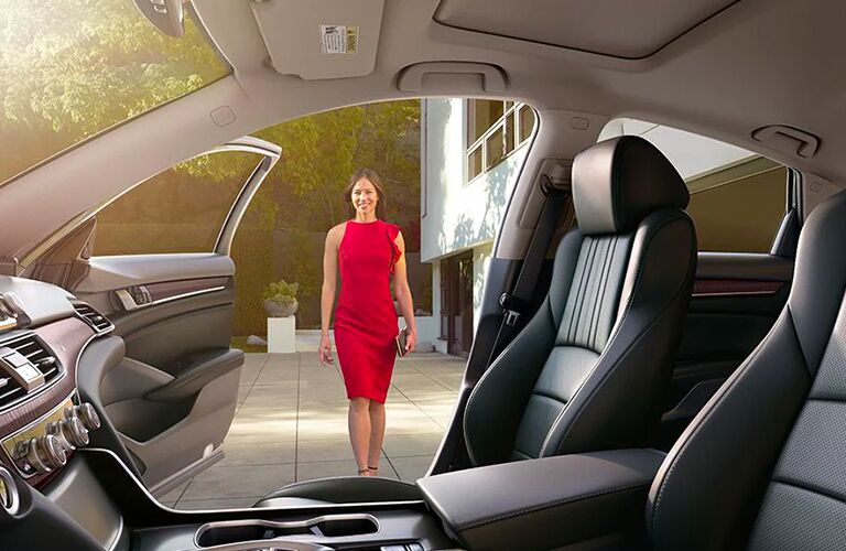 Woman in a red dress approaches the open passenger door and waiting interior of a 2020 Honda Accord.