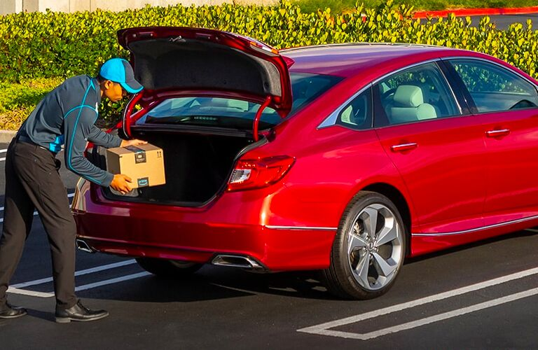 Human loads a mysterious small box into the open trunk of a red 2020 Honda Accord.