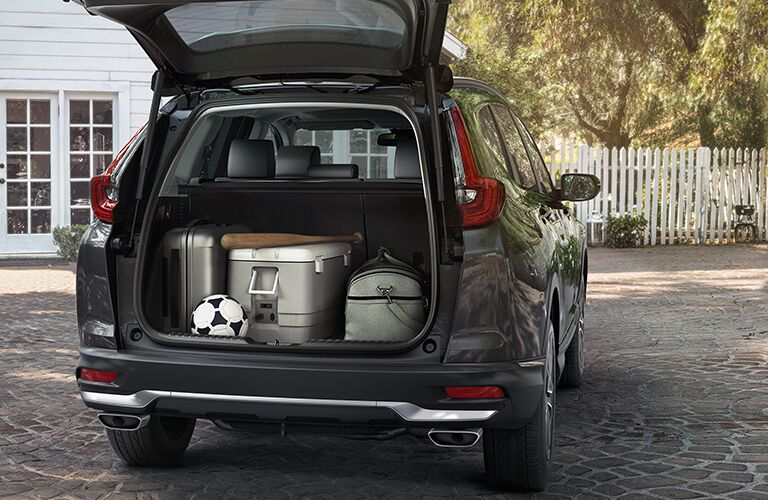 Wide open cargo hatch filled with miscellaneous family items on a 2020 Honda CR-V.