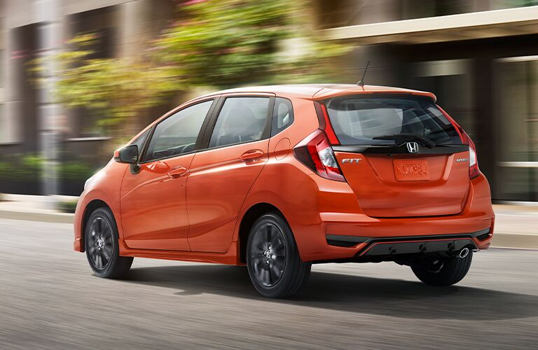 Rear side angled look at an orange 2020 Honda Fit as it drives away up a city street
