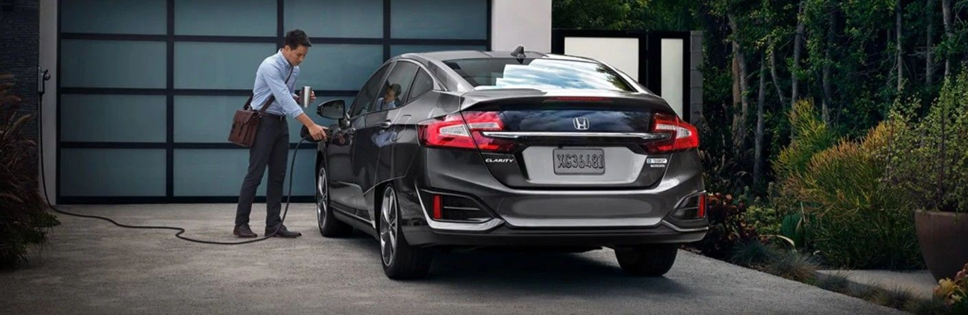 Man charges up Honda Clarity Plug-In Hybrid with a plug