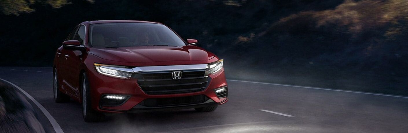 Red 2021 Honda Insight drives up a highway