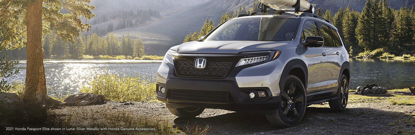 "2021 Honda Passport in woods. Text reads, ""Honda Passport Elite shown in Lunar Silver Metallic with Honda Genuine Accessories."""