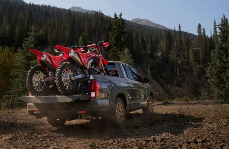 Two dirtbikes in the bed of a 2021 Honda Ridgeline