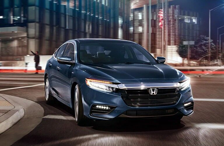 Blue 2022 Honda Insight rounds a corner at night in a city