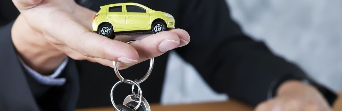 A car key chain and a yellow toy car