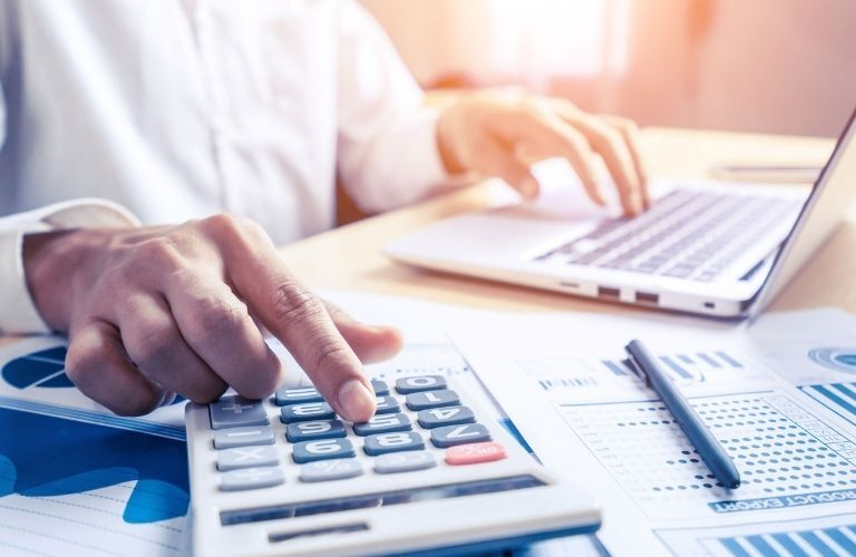 A man working on a calculator and a laptop