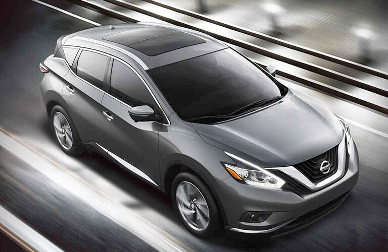 Silver 2017 Nissan Murano cruises up a highway in the clouds.