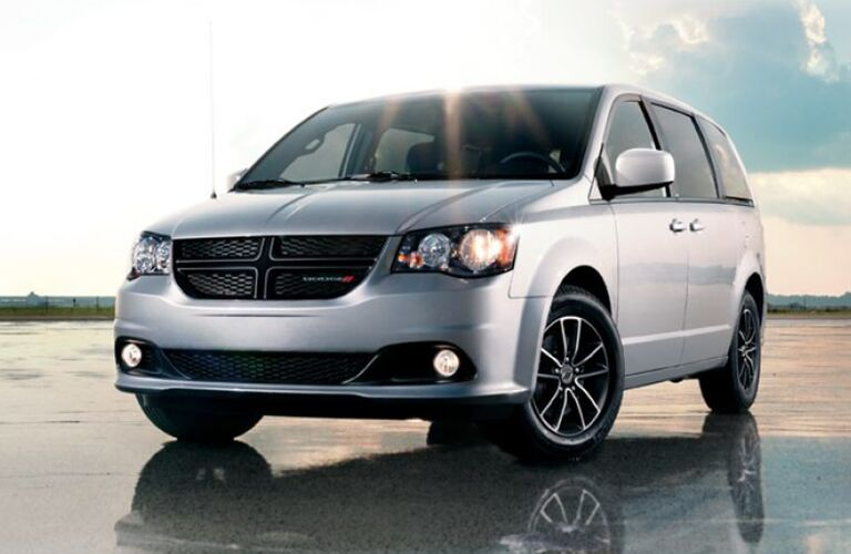 Silver 2019 Dodge Grand Caravan parked on a reflective surface.