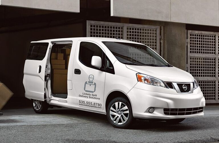 side view of a white 2019 Nissan NV200 with its side door open and packages inside