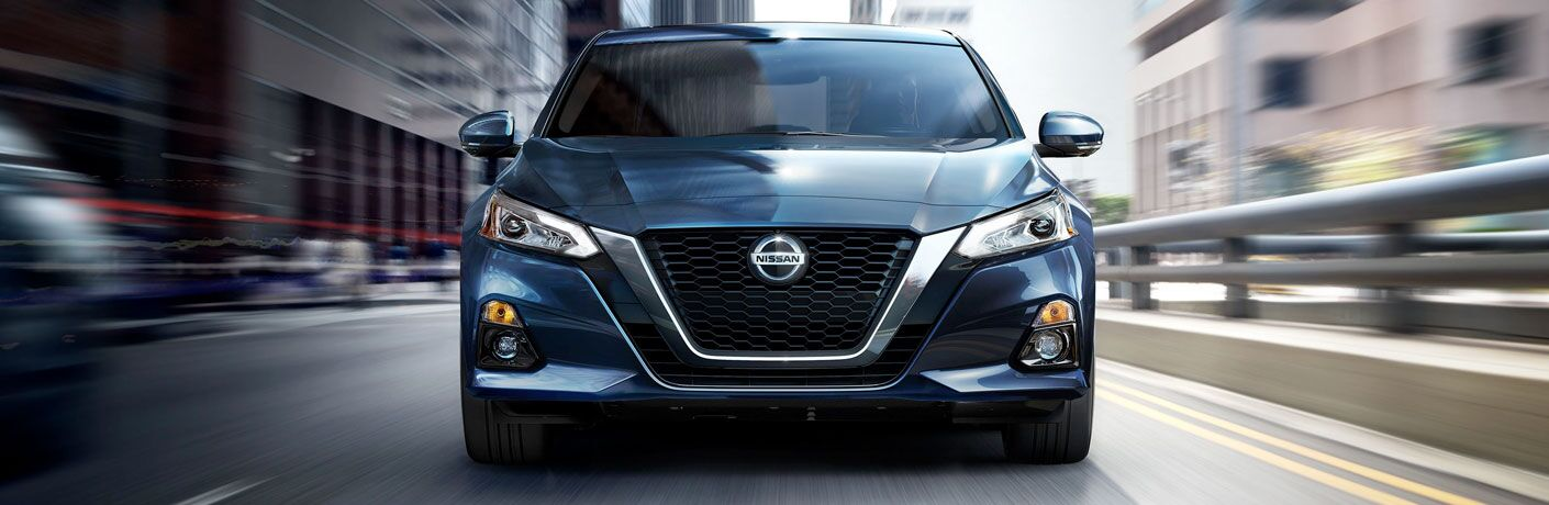 Head-on view of a 2020 Nissan Altima driving up a highway as the road blurs around it.