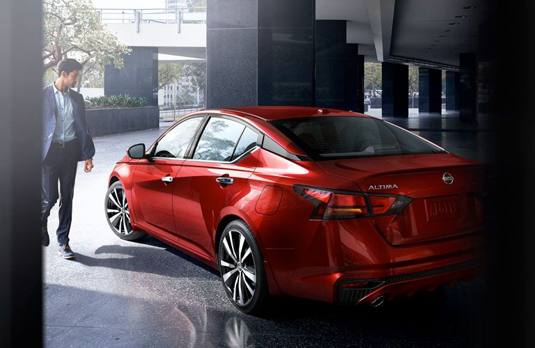 A well-dressed man approaches a red 2020 Nissan Altima in a sleek parking area.