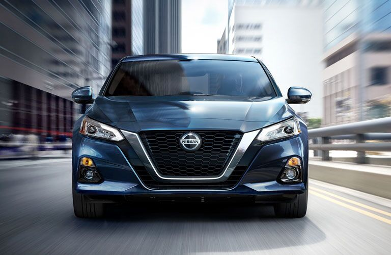 Head-on view of a blue 2020 Nissan Altima driving through a city.
