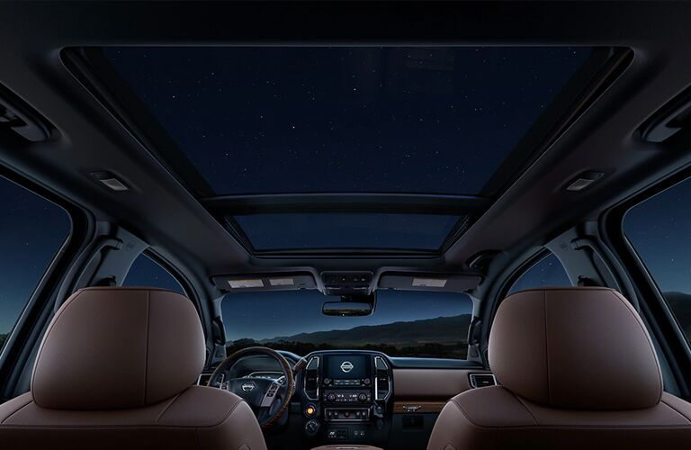 Interior of 2020 Nissan TITAN, with a panoramic sunroof, at night in the desert