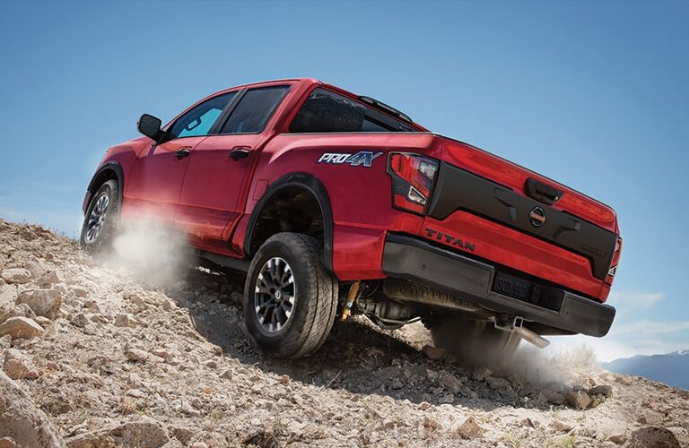 Red 2020 Nissan TITAN ruggedly climbs a pile of dirt