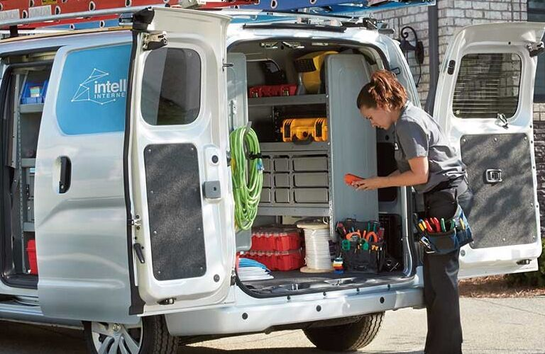 Woman retrieves items from the back of a 2020 Nissan NV200