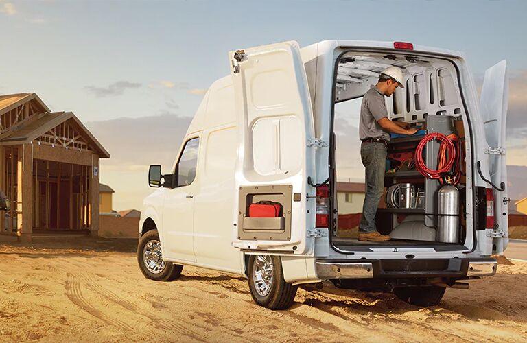 Man inside 2021 Nissan NV Cargo Van with the doors wide open