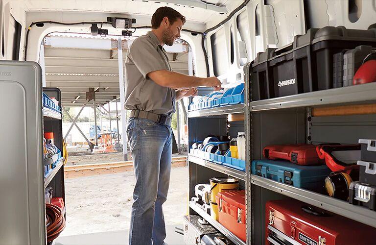 Man looks at a tool inside 2021 Nissan NV Cargo Van