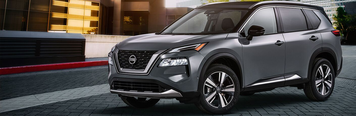 Silver 2021 Nissan Rogue by a spunky building