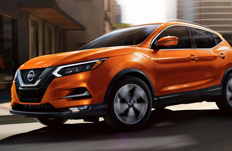 Low-angled front/side view of an orange 2021 Nissan Rogue Sport