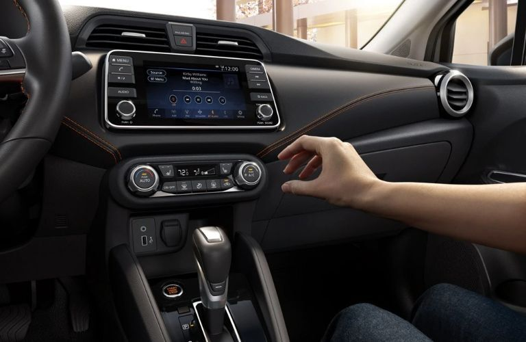 Hand reaches for dial inside 2021 Nissan Versa