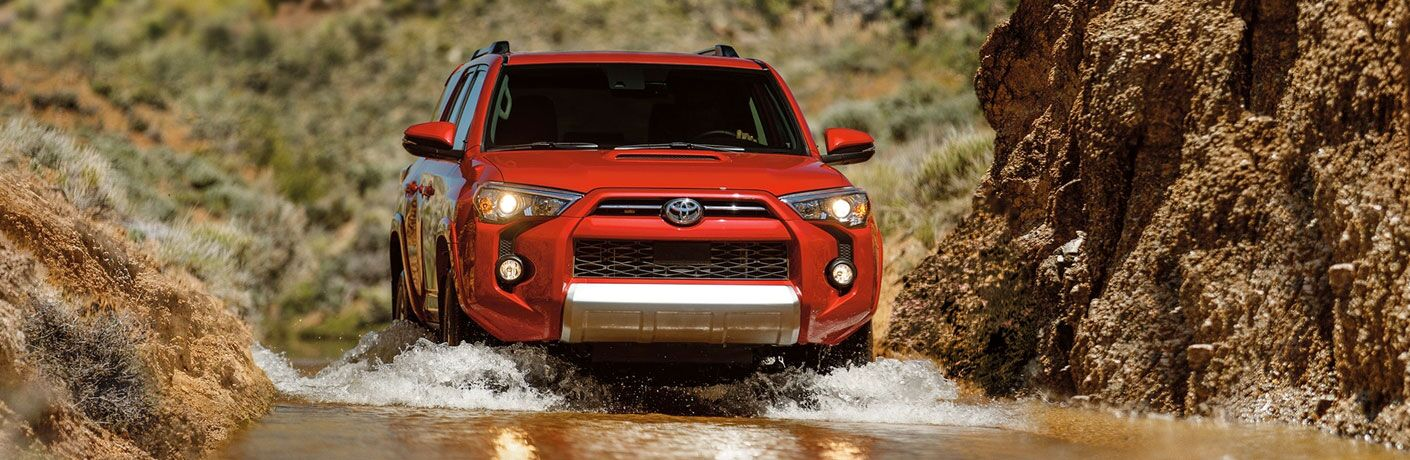Red 2020 Toyota 4Runner plows up a stream.