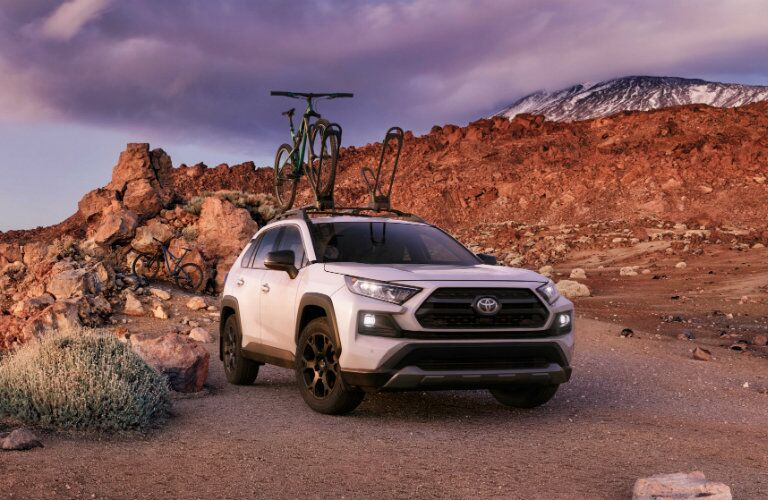 A bicycle is perched atop a white 2020 Toyota RAV4 out in the wilderness.