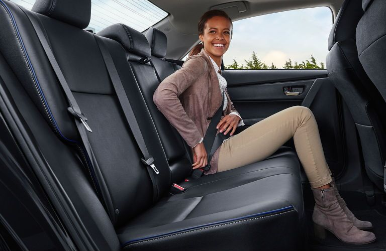 side view of a woman sitting in the rear seat of a 2018 Toyota Corolla