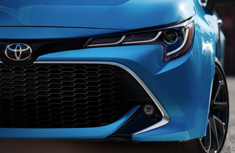 close up of the grille and headlight on a blue 2019 Toyota Corolla Hatchback