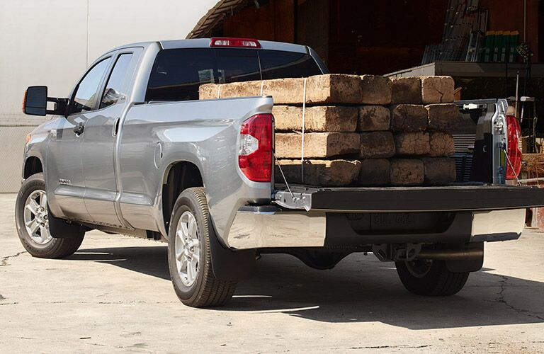 rear view of a silver 2019 Toyota Tundra with a bed full of wood