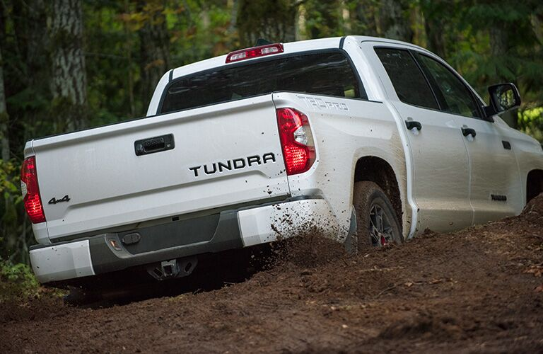 White 2020 Toyota Tundra off-roads through dirt in a forest.