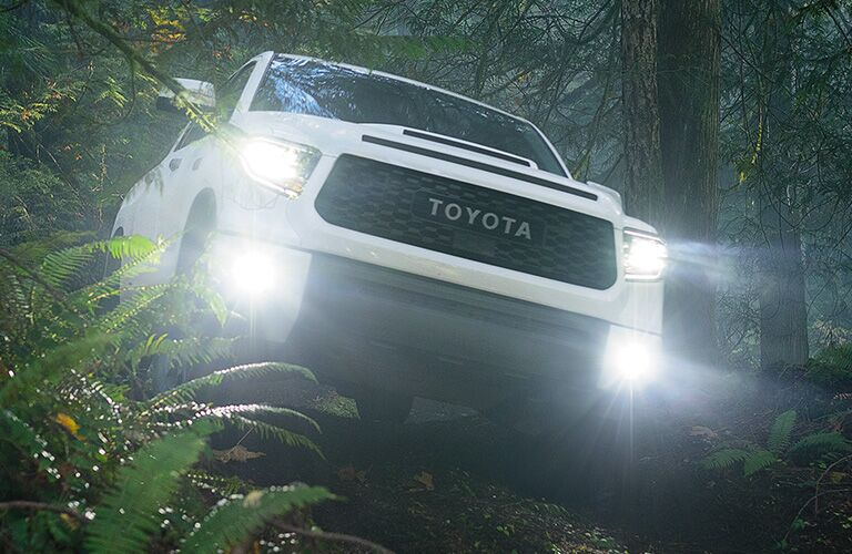 2020 Toyota Tundra comes over a hill in a forest.
