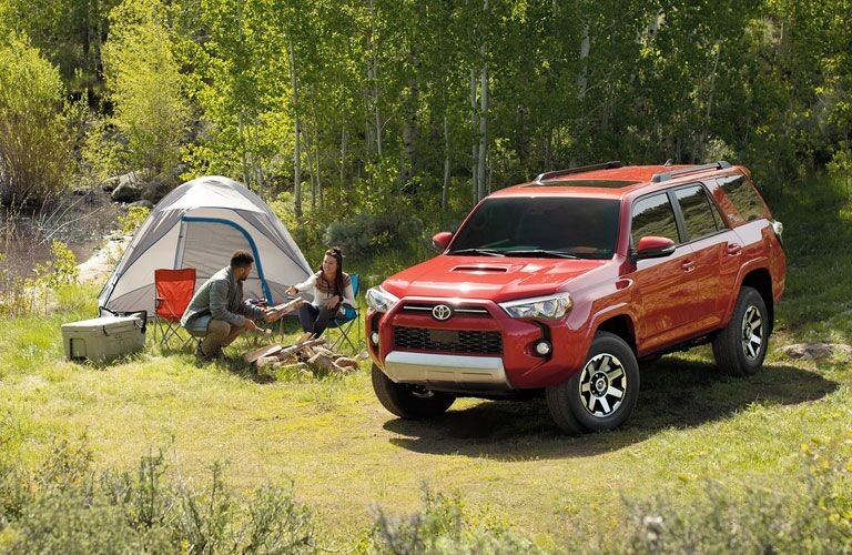 Red 2020 Toyota 4Runner parked at a campsite with a couple.