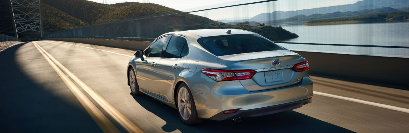 Silver 2020 Toyota Camry drives on a highway alongside a body of water.