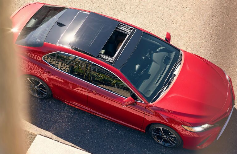 Red 2020 Toyota Camry with an open sunroof, viewed from above.