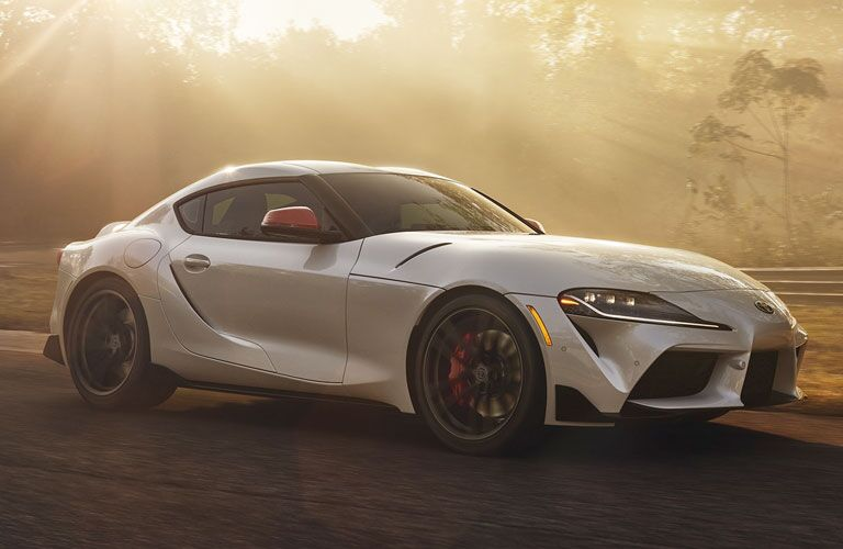 White 2020 Toyota Supra drives along a track on a sunny day.