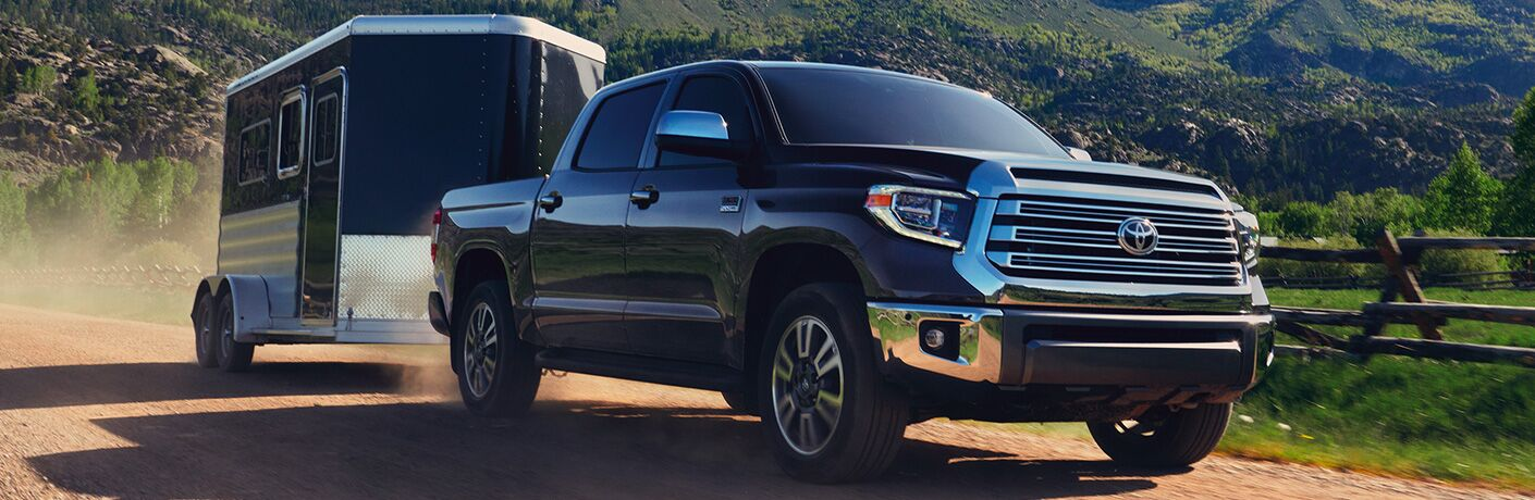 2020 Toyota Tundra tows a small camper up a dirt path.